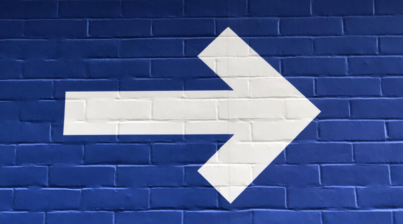 White arrow on a blue brick wall pointing forward, toward finding meaning.